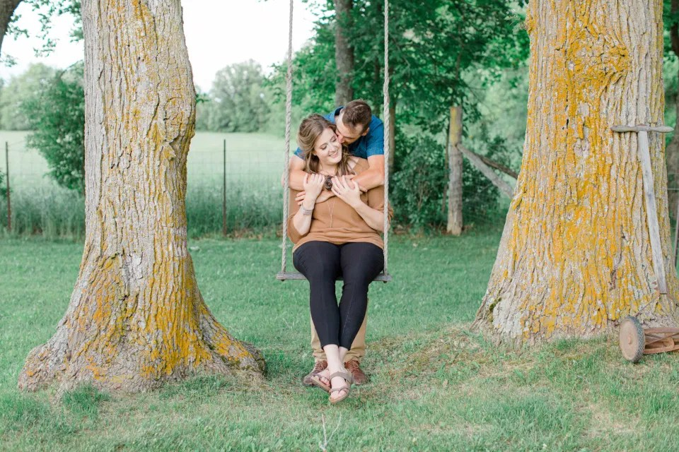 Swing between Trees - Engagement Session - Cow - Engagement Session Must Have Shot - Cows during Engagement Session - Poses during Engagement Session  Sunset - Natural Posing for Photo Session - Couples Photo Session Fun - Fun on the Farm - Farm Engagement Session - Blue and Brown Engagement Session Inspiration - Natural Engagement Session Posing - Ideas for what to wear for Engagement Photography, Modern Engagement Session Inspiration Wardrobe Ideas. Unsure of what to wear for your engagement photos, we've got you! Romantic brown with black leggings for Summer Engagement in Almonte. Grey Loft Studio is Ottawa's Wedding and Engagement Photographer for Real couples, showcasing photos that are modern, bright, and fun.