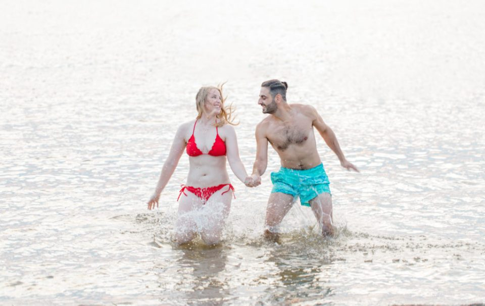 Cute Poses on the beach in Water - Ideas for what to wear for Engagement Photography, Modern Engagement Session Inspiration Wardrobe Ideas. Unsure of what to wear for your engagement photos, we've got you! Teal Board Shorts and Red Bikini -  Engagement at Britannia Beach, Nepean. Grey Loft Studio is Ottawa's Wedding and Engagement Photographer Videographer for Real couples, showcasing photos that are modern, bright, and fun.