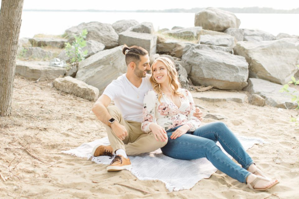 Sitting on the Beach - Ideas for what to wear for Engagement Photography, Modern Engagement Session Inspiration Wardrobe Ideas. Unsure of what to wear for your engagement photos, we've got you! Romantic floral shirt & jeans.  White T-shirt & neutral pants . Boat Shoes and Fancy. beaded sandals. Engagement at Petrie Island, Orleans. Grey Loft Studio is Ottawa's Wedding and Engagement Photographer Videographer for Real couples, showcasing photos that are modern, bright, and fun.