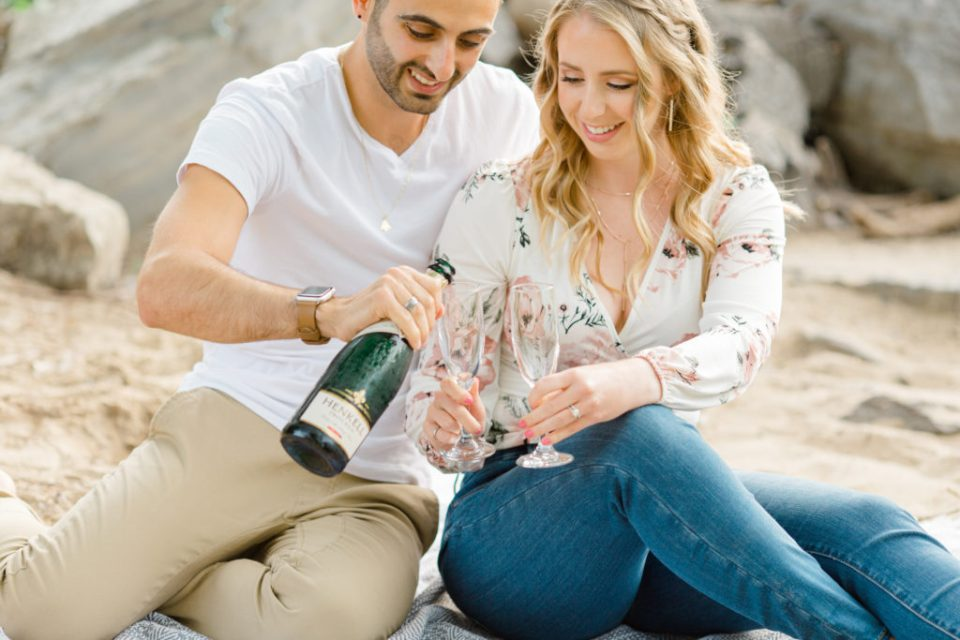 Pouring Champagne - Sitting on the Beach - Ideas for what to wear for Engagement Photography, Modern Engagement Session Inspiration Wardrobe Ideas. Unsure of what to wear for your engagement photos, we've got you! Romantic floral shirt & jeans.  White T-shirt & neutral pants . Boat Shoes and Fancy. beaded sandals. Engagement at Petrie Island, Orleans. Grey Loft Studio is Ottawa's Wedding and Engagement Photographer Videographer for Real couples, showcasing photos that are modern, bright, and fun.