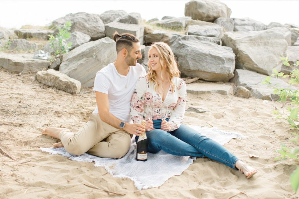 Drink the champagne - Sitting on the Beach - Ideas for what to wear for Engagement Photography, Modern Engagement Session Inspiration Wardrobe Ideas. Unsure of what to wear for your engagement photos, we've got you! Romantic floral shirt & jeans.  White T-shirt & neutral pants . Boat Shoes and Fancy. beaded sandals. Engagement at Petrie Island, Orleans. Grey Loft Studio is Ottawa's Wedding and Engagement Photographer Videographer for Real couples, showcasing photos that are modern, bright, and fun.