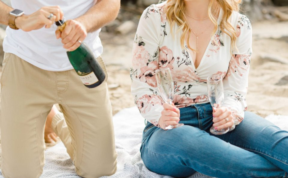 Pop Champagne -Sitting on the Beach - Ideas for what to wear for Engagement Photography, Modern Engagement Session Inspiration Wardrobe Ideas. Unsure of what to wear for your engagement photos, we've got you! Romantic floral shirt & jeans.  White T-shirt & neutral pants . Boat Shoes and Fancy. beaded sandals. Engagement at Petrie Island, Orleans. Grey Loft Studio is Ottawa's Wedding and Engagement Photographer Videographer for Real couples, showcasing photos that are modern, bright, and fun.