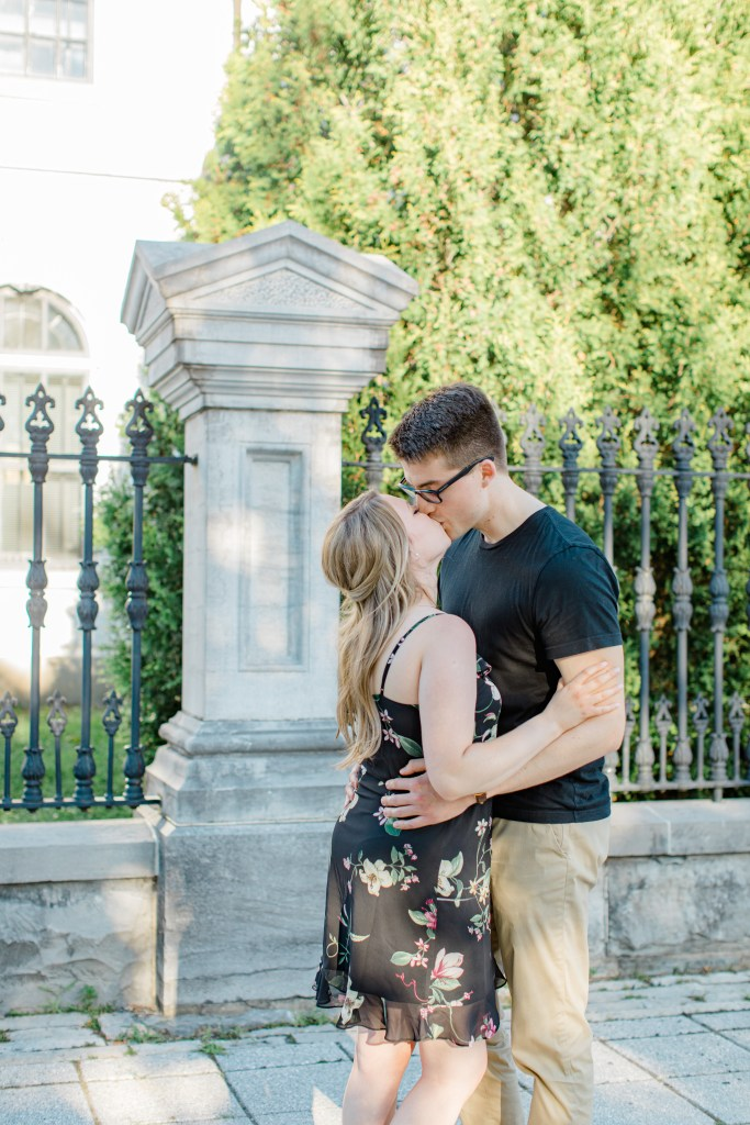 Kissing while Standing at Rideau Hall - Ideas for what to wear for Engagement Photography, Modern Engagement Session Inspiration Wardrobe Ideas. Unsure of what to wear for your engagement photos, we've got you! Romantic floral dress. Black Polo T-shirt & neutral pants . Boat Shoes and Fancy beaded wedges. Engagement downtown Ottawa. Grey Loft Studio is Ottawa's Wedding and Engagement Photographer Videographer for Real couples, showcasing photos that are modern, bright, and fun.
