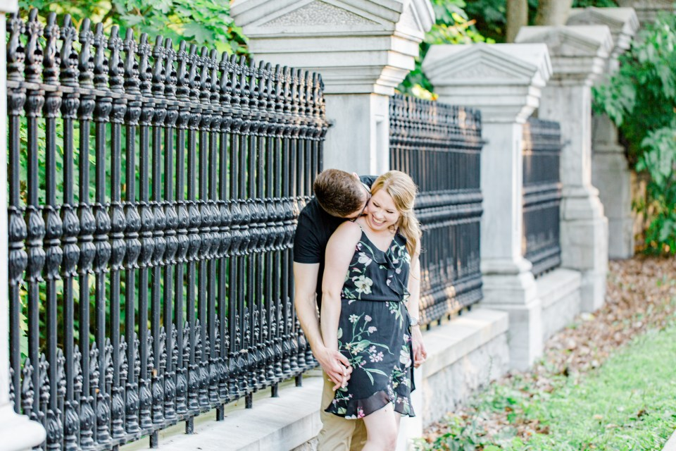 Kissing the Neck - Holding Hands Shot - Engagement Photo Poses- Posing while at Rideau Hall - Ideas for what to wear for Engagement Photography, Modern Engagement Session Inspiration Wardrobe Ideas. Unsure of what to wear for your engagement photos, we've got you! Romantic floral dress. Black Polo T-shirt & neutral pants . Boat Shoes and Fancy beaded wedges. Engagement downtown Ottawa. Grey Loft Studio is Ottawa's Wedding and Engagement Photographer Videographer for Real couples, showcasing photos that are modern, bright, and fun.