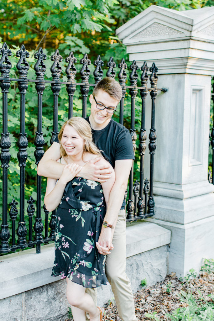 Cute Posing for Tall guys with short girls - Holding Hands Shot - Engagement Photo Poses- Posing while at Rideau Hall - Ideas for what to wear for Engagement Photography, Modern Engagement Session Inspiration Wardrobe Ideas. Unsure of what to wear for your engagement photos, we've got you! Romantic floral dress. Black Polo T-shirt & neutral pants . Boat Shoes and Fancy beaded wedges. Engagement downtown Ottawa. Grey Loft Studio is Ottawa's Wedding and Engagement Photographer Videographer for Real couples, showcasing photos that are modern, bright, and fun.