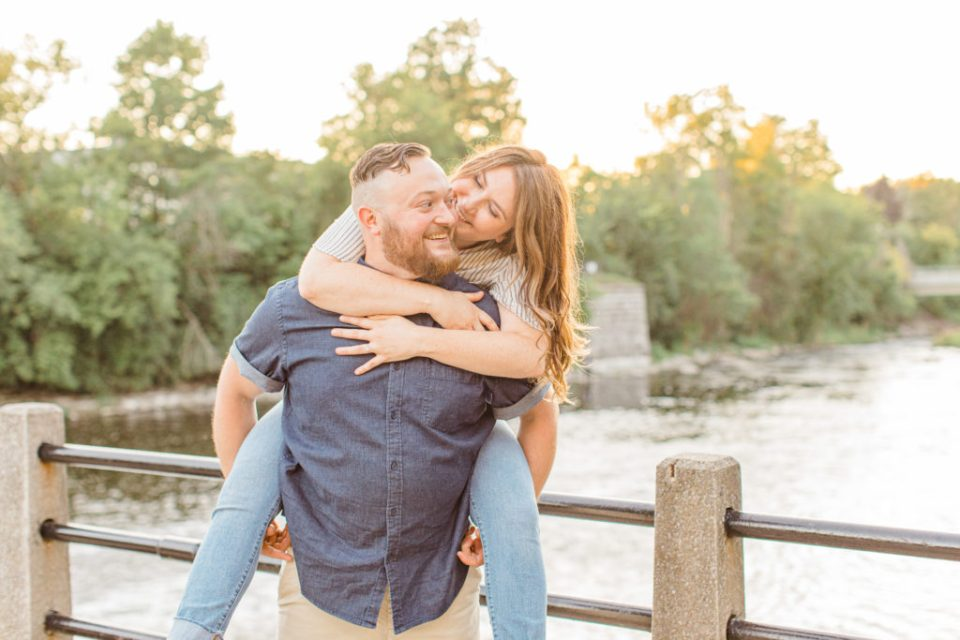 Piggy Back Pose during Engagement Session - Watson's Mill Engagement Session Manotick - Bright & Airy photography - Grey Loft Studio - Ottawa Wedding Photographer - Ottawa Wedding Videographer - Engagement Session Locations in Ottawa - Summer Engagement session - Light blue and Cream with casual jeans and strap sandals. Ottawa Photo Studio.
