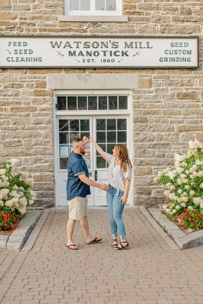 Spinning during engagement Session - Watson's Mill Engagement Session Manotick - Bright & Airy photography - Grey Loft Studio - Ottawa Wedding Photographer - Ottawa Wedding Videographer - Engagement Session Locations in Ottawa - Summer Engagement session - Light blue and Cream with casual jeans and strap sandals. Ottawa Photo Studio.