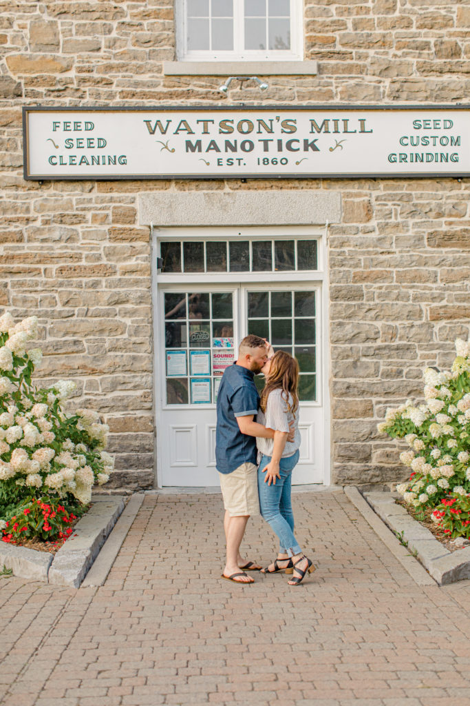 Couple Kissing during engagement session - Watson's Mill Engagement Session Manotick - Bright & Airy photography - Grey Loft Studio - Ottawa Wedding Photographer - Ottawa Wedding Videographer - Engagement Session Locations in Ottawa - Summer Engagement session - Light blue and Cream with casual jeans and strap sandals. Ottawa Photo Studio.