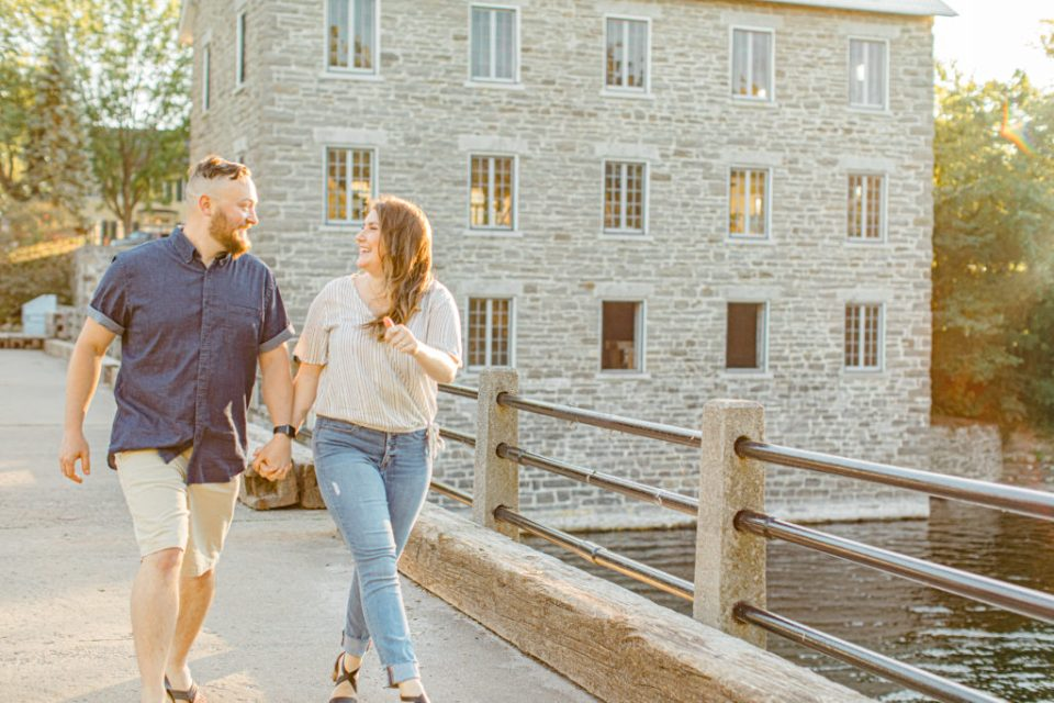 Couple holding each other close and walking -engagement session - Watson's Mill Engagement Session Manotick - Bright & Airy photography - Grey Loft Studio - Ottawa Wedding Photographer - Ottawa Wedding Videographer - Engagement Session Locations in Ottawa - Summer Engagement session - Light blue and Cream with casual jeans and strap sandals. Ottawa Photo Studio.