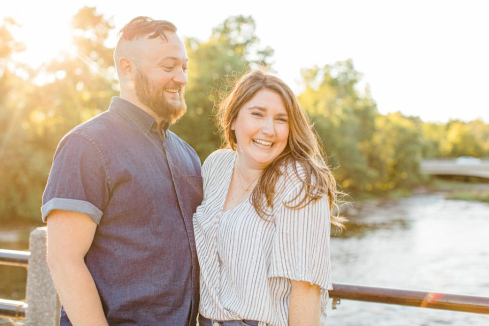 Couple holding each other close -engagement session - Watson's Mill Engagement Session Manotick - Bright & Airy photography - Grey Loft Studio - Ottawa Wedding Photographer - Ottawa Wedding Videographer - Engagement Session Locations in Ottawa - Summer Engagement session - Light blue and Cream with casual jeans and strap sandals. Ottawa Photo Studio.