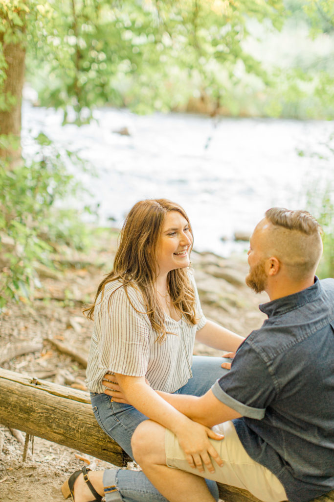 Having fun during engagement session as a couple - sitting on a log
