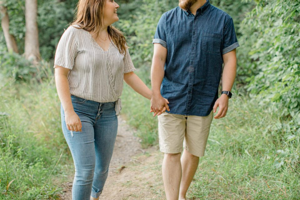 Couple Holding hands during engagement session - Watson's Mill Engagement Session Manotick - Bright & Airy photography - Grey Loft Studio - Ottawa Wedding Photographer - Ottawa Wedding Videographer - Engagement Session Locations in Ottawa - Summer Engagement session - Light blue and Cream with casual jeans and strap sandals. Ottawa Photo Studio.