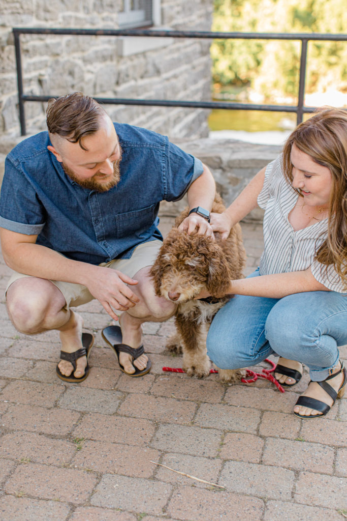 Chocolate Golden Doodle Puppy - grey loft studio - Couple holding each other close and walking looking back -engagement session - Watson's Mill Engagement Session Manotick - Bright & Airy photography - Grey Loft Studio - Ottawa Wedding Photographer - Ottawa Wedding Videographer - Engagement Session Locations in Ottawa - Summer Engagement session - Light blue and Cream with casual jeans and strap sandals. Ottawa Photo Studio.