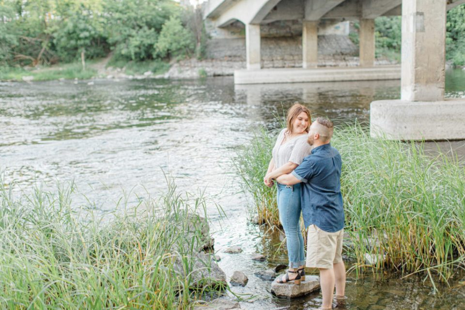 Braving the water - Watson's Mill Engagement Session Manotick - Bright & Airy photography - Grey Loft Studio - Ottawa Wedding Photographer - Ottawa Wedding Videographer - Engagement Session Locations in Ottawa - Summer Engagement session - Light blue and Cream with casual jeans and strap sandals. Ottawa Photo Studio.