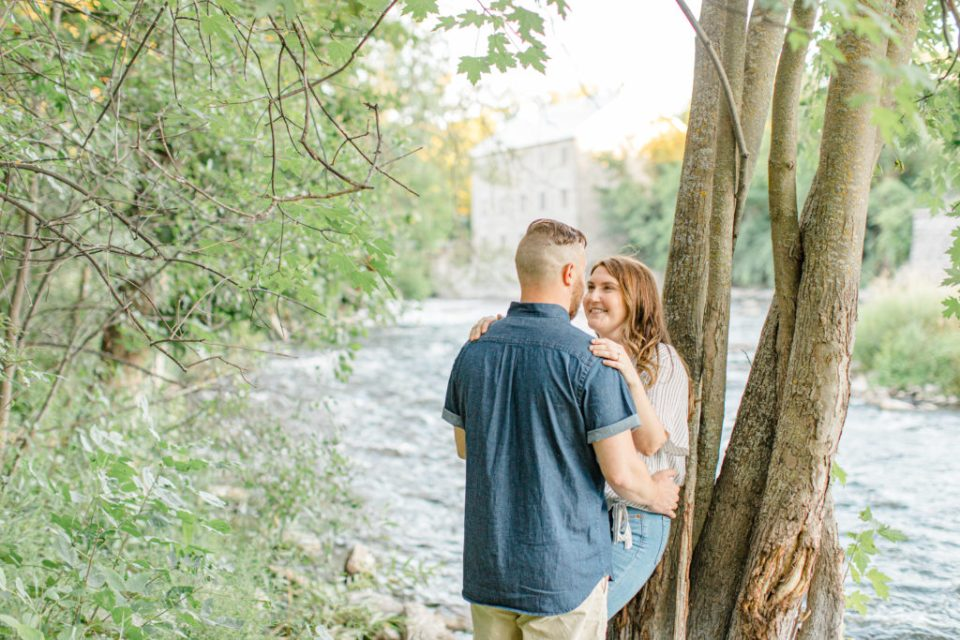 Look at each other and smile - by the water - Watson's Mill Engagement Session Manotick - Bright & Airy photography - Grey Loft Studio - Ottawa Wedding Photographer - Ottawa Wedding Videographer - Engagement Session Locations in Ottawa - Summer Engagement session - Light blue and Cream with casual jeans and strap sandals. Ottawa Photo Studio.