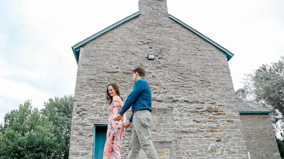 Couple walking near ruins -Ideas for what to wear for Engagement Photography, Modern Engagement Session Inspiration Wardrobe Ideas. Unsure of what to wear for your engagement photos, we've got you! Romantic white with Pink Flower dress for Summer Engagement in Ottawa. Grey Loft Studio is Ottawa's Wedding and Engagement Photographer for Real couples, showcasing photos that are modern, bright, and fun. Pinhey's Point Dunrobin.