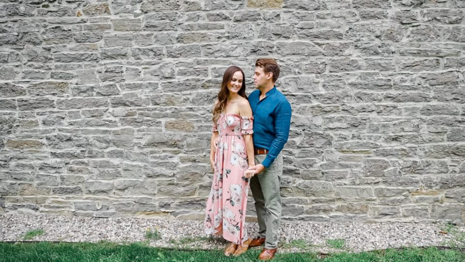 Standing in front of Brick Wall - Ideas for what to wear for Engagement Photography, Modern Engagement Session Inspiration Wardrobe Ideas. Unsure of what to wear for your engagement photos, we've got you! Romantic white with Pink Flower dress for Summer Engagement in Ottawa. Grey Loft Studio is Ottawa's Wedding and Engagement Photographer for Real couples, showcasing photos that are modern, bright, and fun. Pinhey's Point Dunrobin.