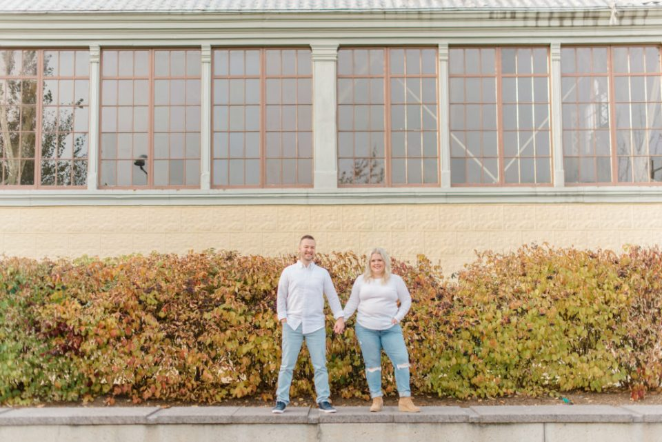 man and woman also husband and wife posing in downtown Ottawa at Lansdowne park wearing white shirts and blue jeans in front of a yellow building with big windows
