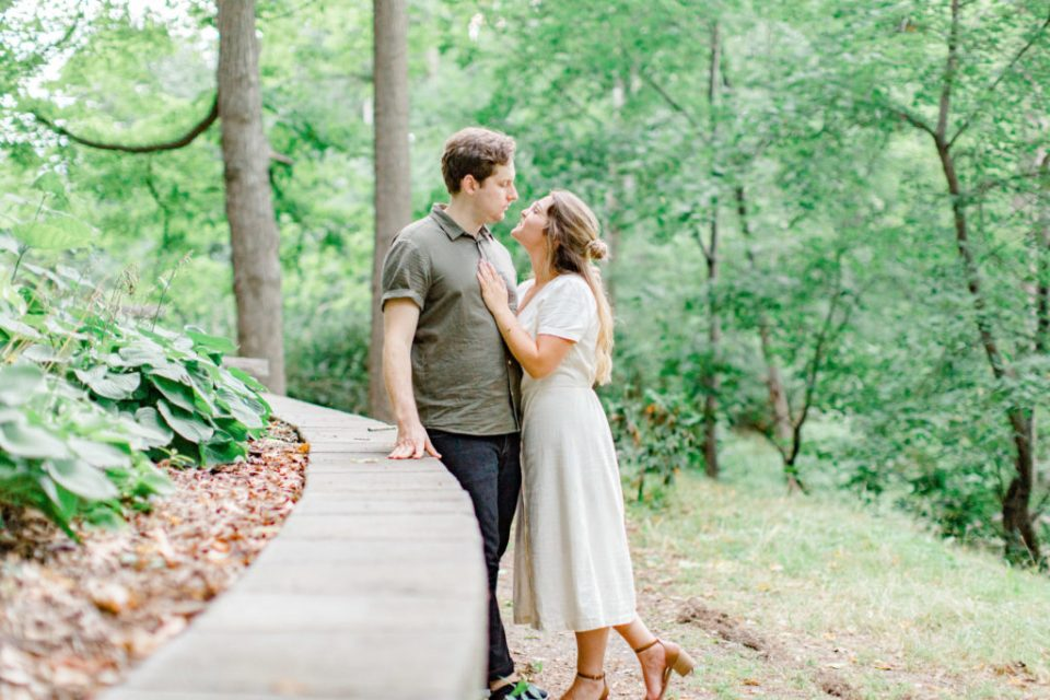 Cute Couple posing during an Engagement Session - Neutral colours - Long white Linen Dress paired with Tan open toed heels. Hair half up half down. Posing at the Ottawa Arboretum - Grey Loft Studio - Ottawa Wedding Photographer - Ottawa Wedding Videographer