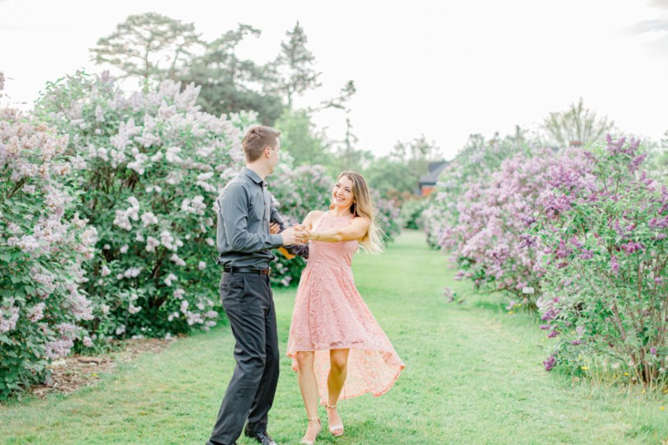 Swinging around together - Dance Poses - Pose Ideas for Photos - Couple Photo Ideas - Cute couple having fun! Engagement Photo Poses & ideas - during Engagement Session Ottawa - at the Arboretum in Ottawa.  Pink & Grey, taupe heels, florals, and a charcuterie board. Grey Loft Studio Wedding Photographers & Videographers.