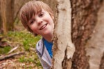 Portrait Of Boy Playing Game In Forest