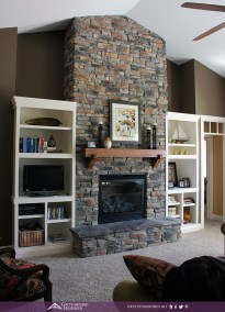 stone fireplace oak mantle shelf built-in bookcases stone to the ceiling