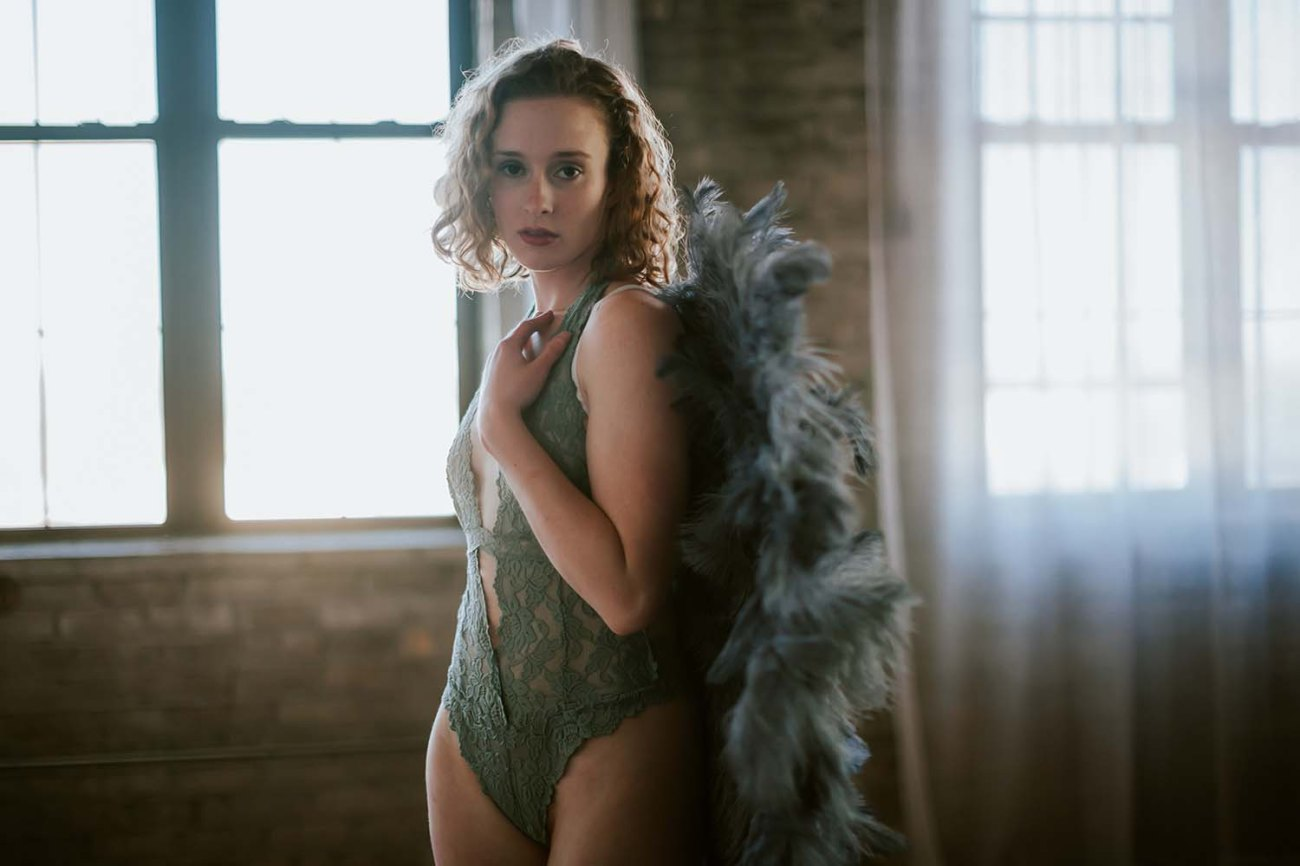 Beautiful redhead in lace bodysuit and angel wings prop Intimate Lifestyle Boudoir Minneapolis Portrait Photographers.