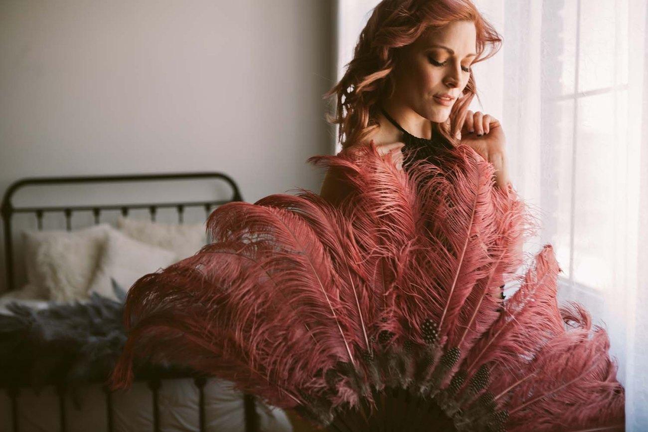 Intimate beauty Boudoir mauve pink burlesque feather fan with natural window light. Twin Cities Boudoir Photographers