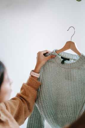 crop woman with sweater on hanger