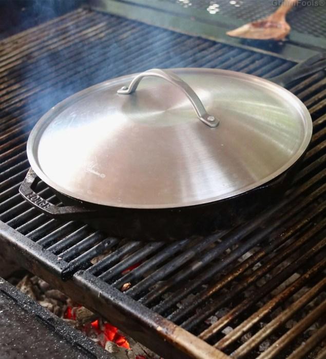 A wok lid on a cast iron skillet