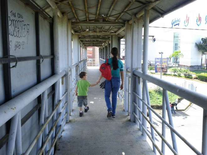 Levi and Roberta walking the elevated pedestrian bridge over the highway to the mall.
