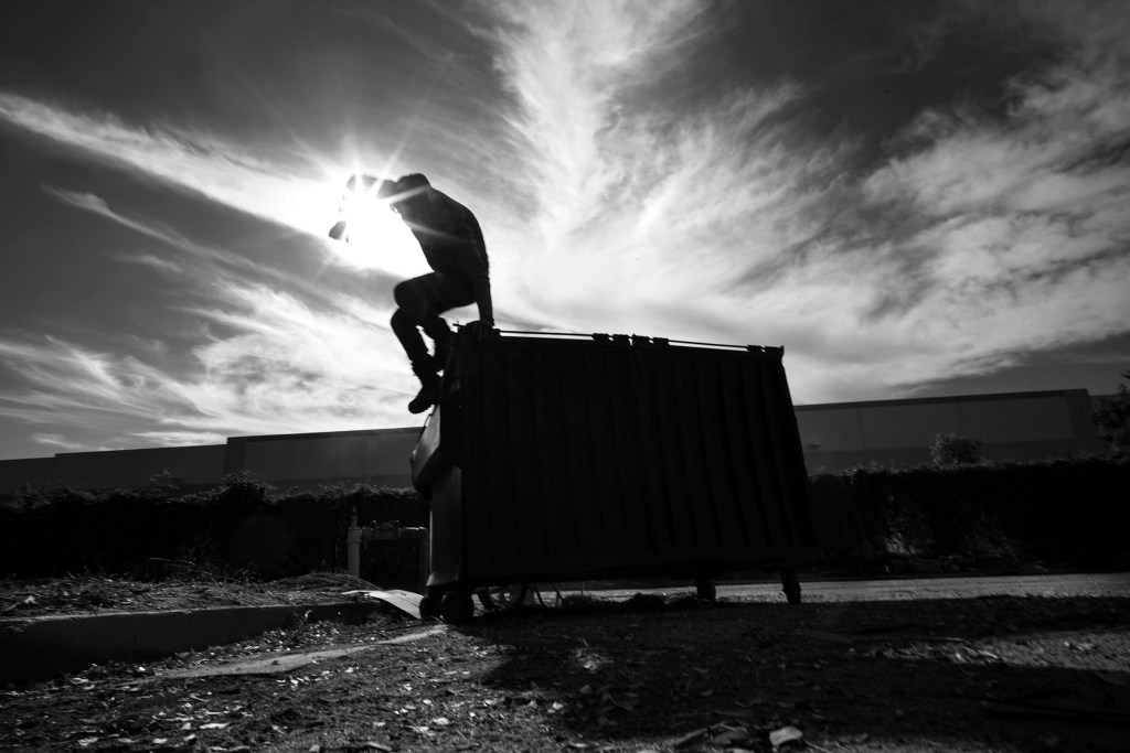 A volunteer Community Garden participant jumps from a trash bin after making room for more waste as he and others clear the land for community garden plots behind a Hillwood Enterprises commercial building.