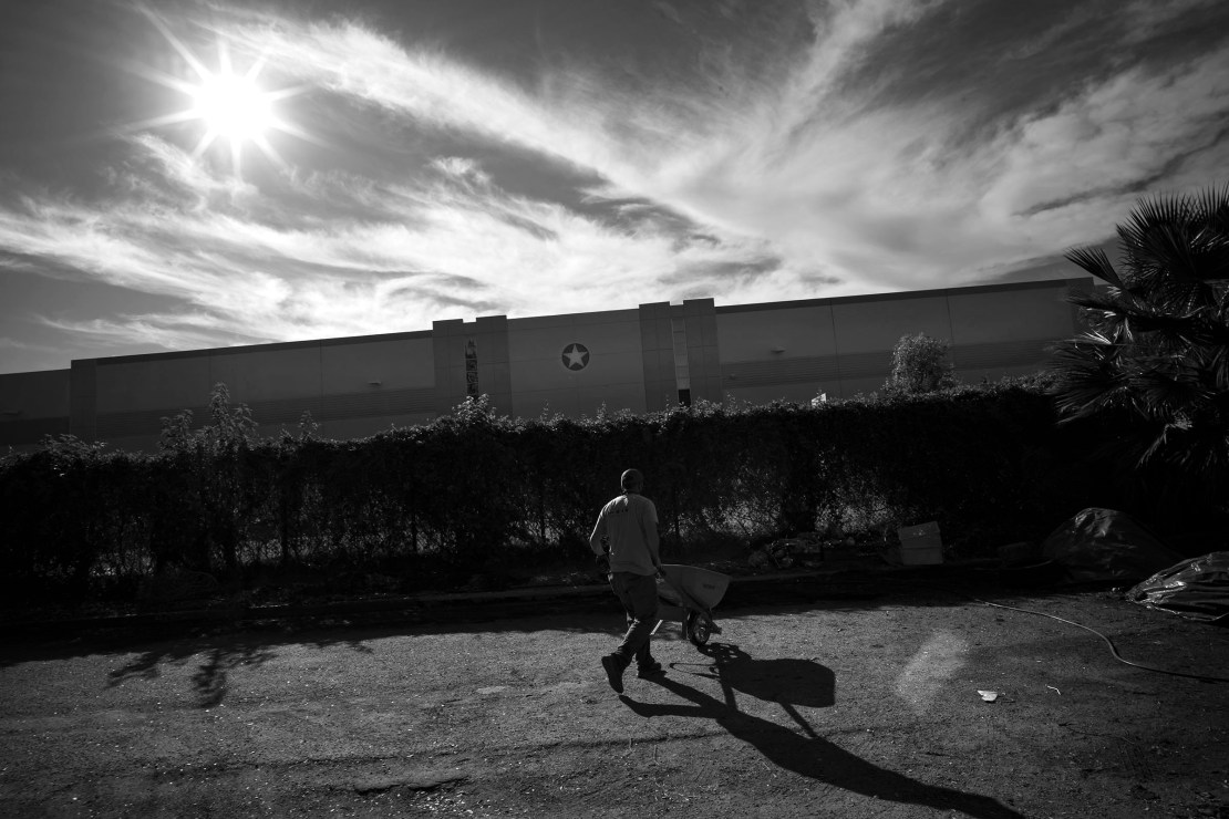A volunteer moves waste in a wheelbarrow behind an adjoining Hillwood Enterprises commercial building.