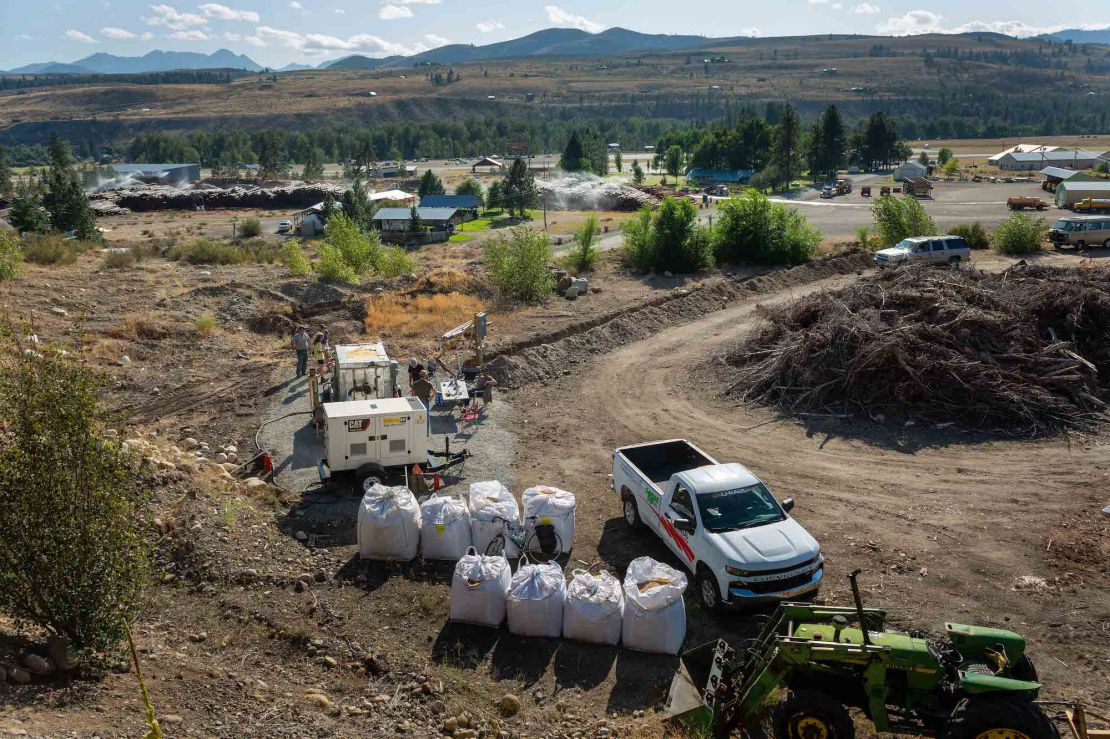 A white pick-up truck is parked next to big, white bags on the side of an unpaved road.