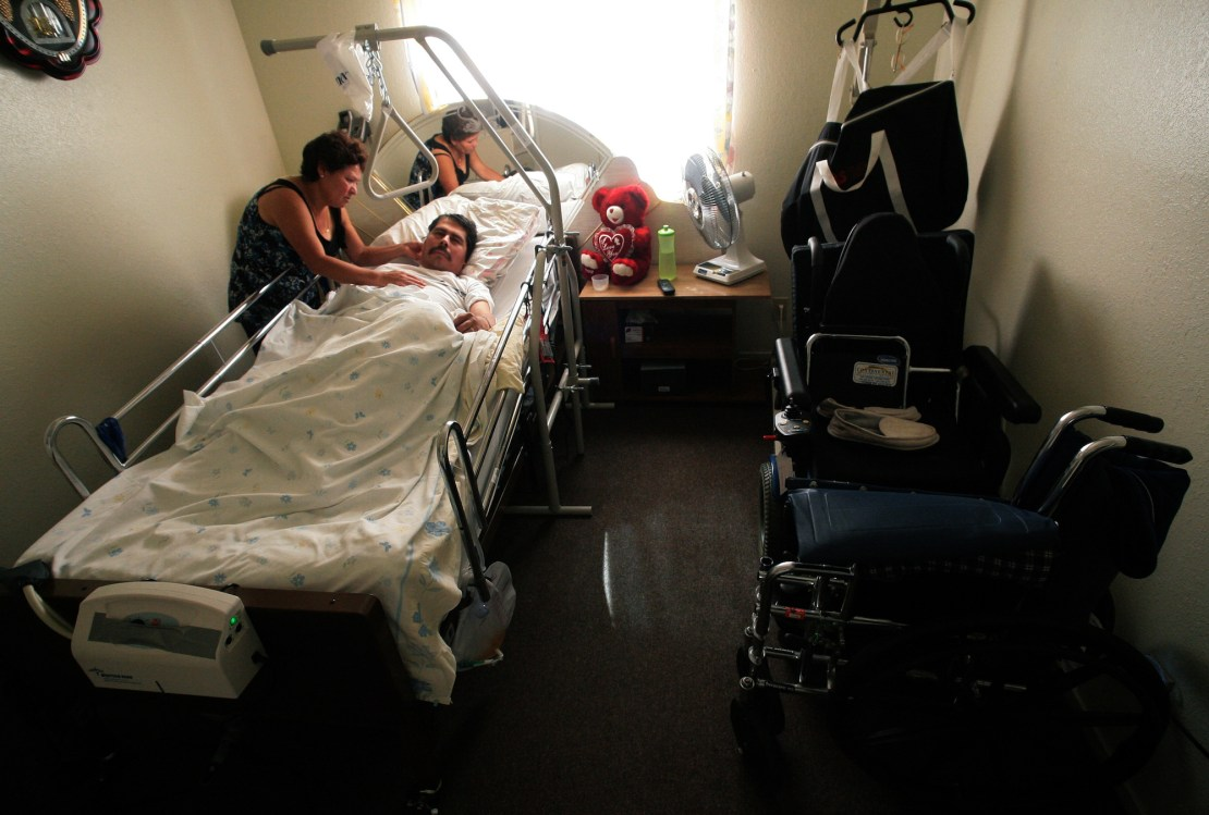 a woman leans over a hospital bed with a man lying in it. The bed is in a small room situated near a window