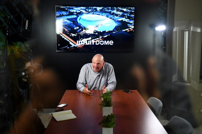 an man in a gray shirt sits at the end of a wooden conference table with a tv showing a stadium interior behind him