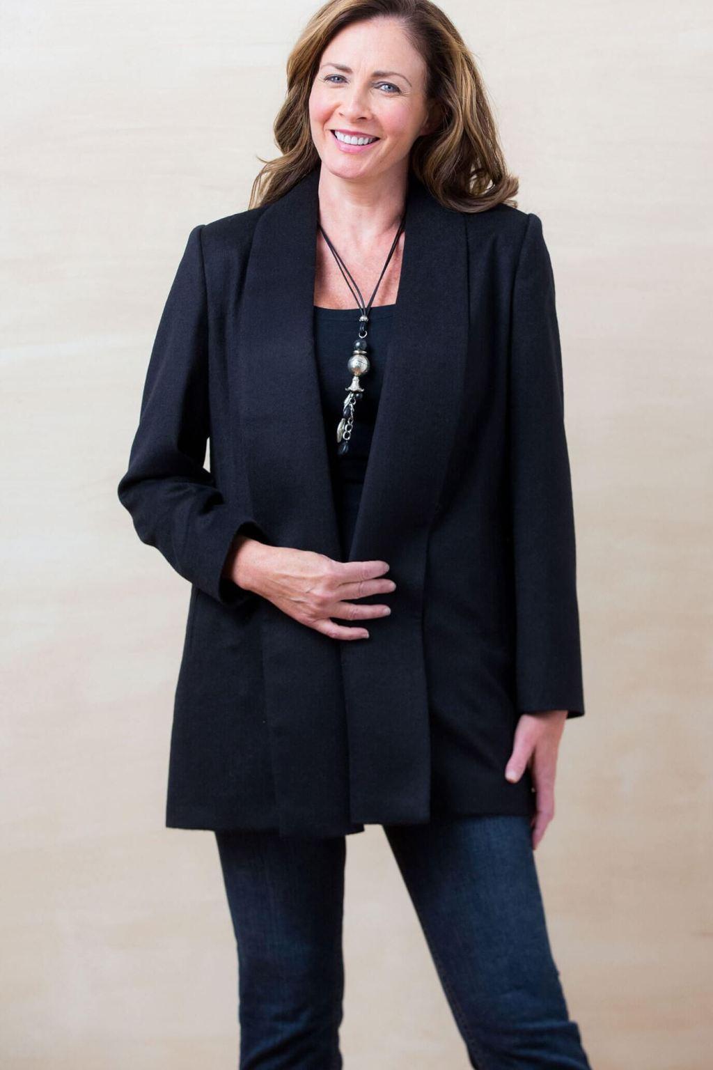 Happy woman wearing black alpaca shawl coat in black