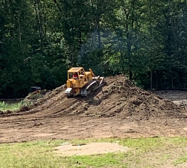 bulldozer on mound of dirt near new pond at grist mill farm