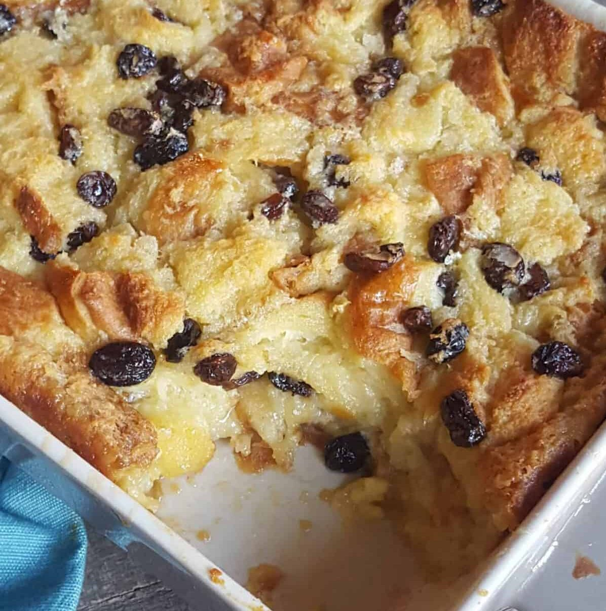 bread pudding with raisins scooped out of a white casserole dish with blue cloth