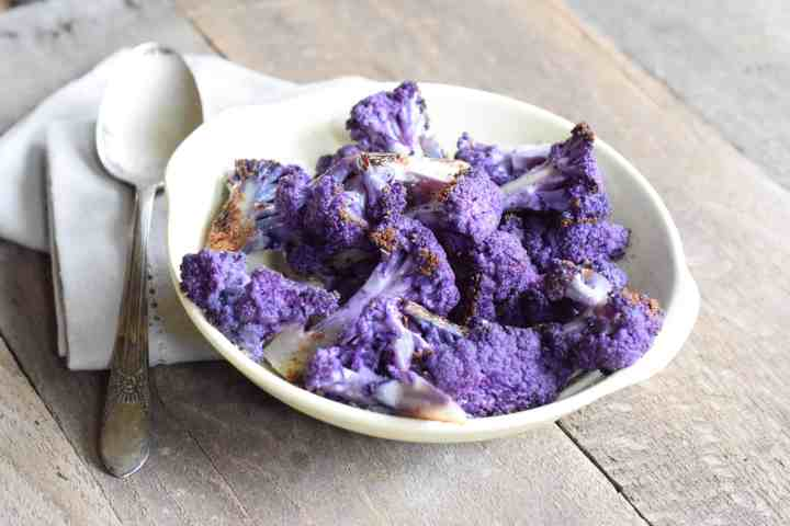 Roasted Purple Cauliflower in a white bowl on light wooden surface