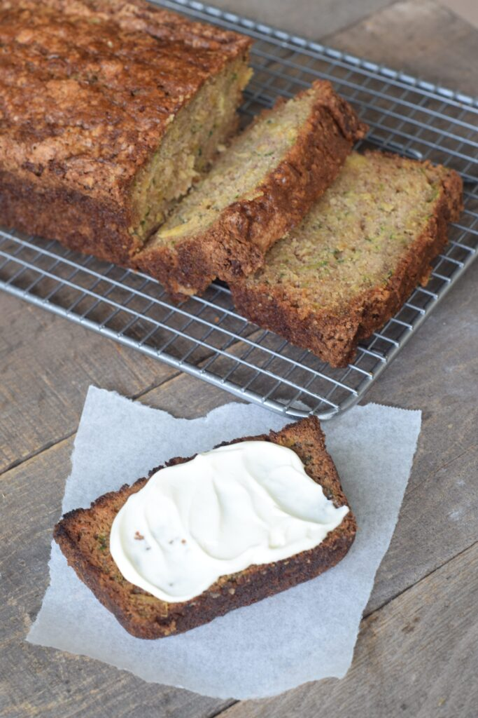 Zucchini Pineapple Bread sliced on a wire rack. One slice toasted and spread with cream cheese on parchment paper