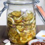 sweet and hot pickles with onions crushed red pepper in a jar