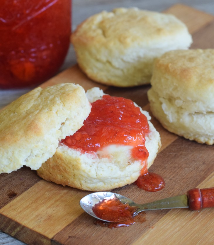 Easy Strawberry Freezer Jam spread on 2 Ingredient Biscuits with jam spilling out of a little wooden spoon on a wooden cutting board.