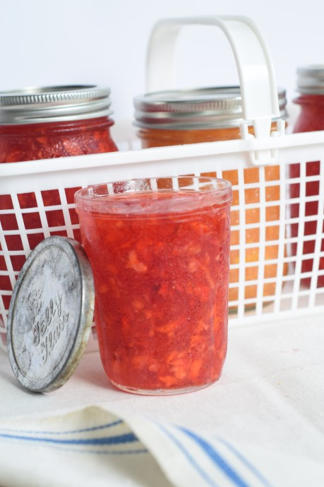 Easy Freezer strawberry jam by a white plastic basic and antique lid propped on the jar