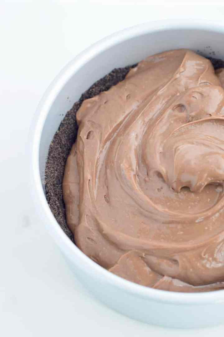 chocolate cheesecake batter dolloped on chocolate crumb crust in a cake pan