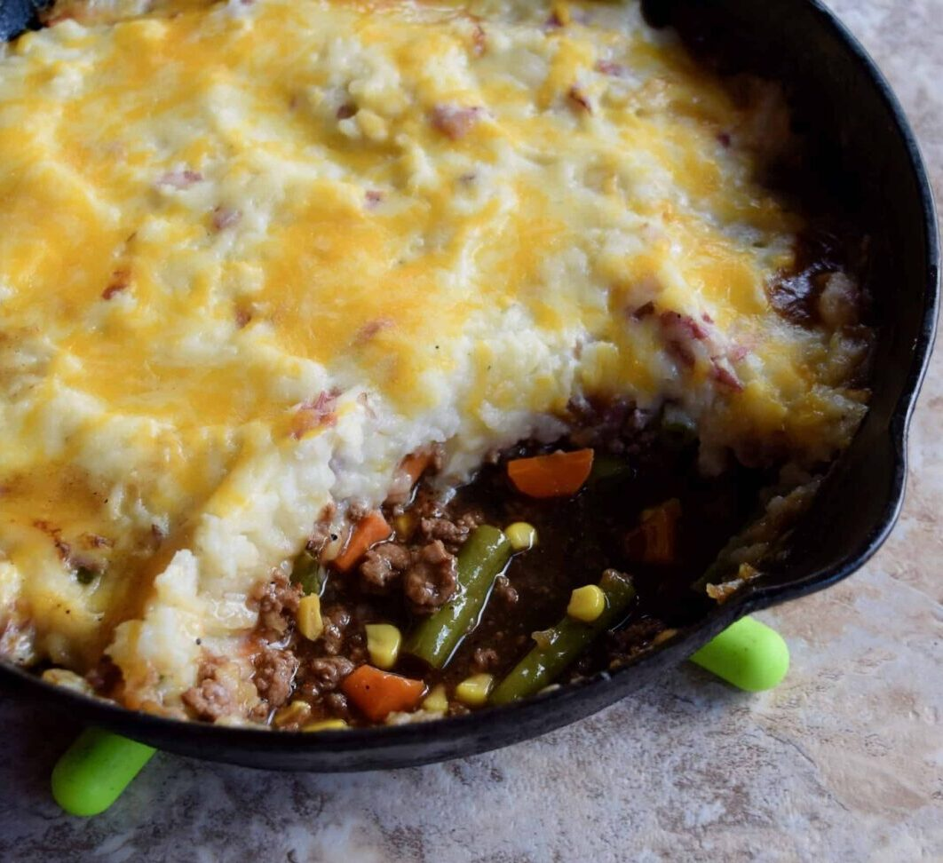 shepherds pie in a cast iron skillet with serving scooped out