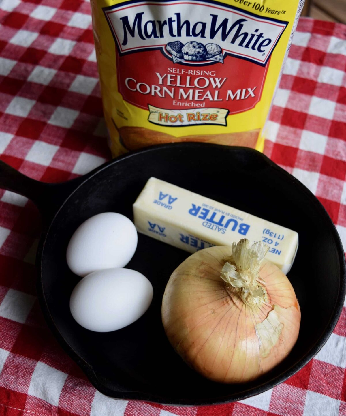bag of martha white cornmeal mix, eggs, vidalia onion, butter in cast iron skillet