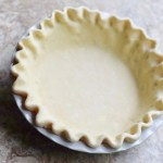 pie crust crimped in a white pie plate