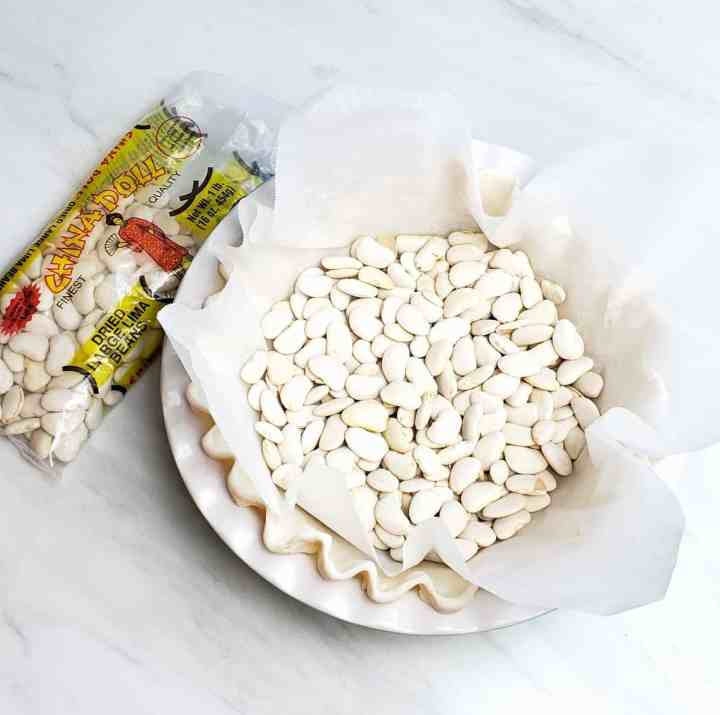 dried lima beans in an unbaked pie crust used as pie weights. Bag of limas next to pie plate