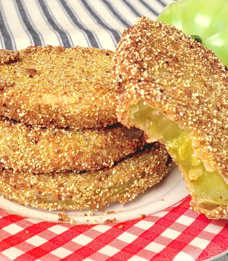 stack of 3 fried green tomatoes with a fourth one with bite out and propped up